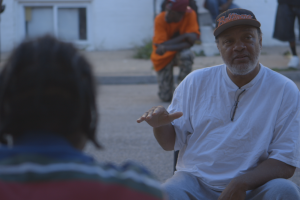 a few Black male Baltimore residents sit together in conversation