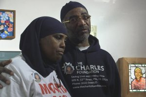 "A still from ""Murders That Matter"": Protagonist Movita Johnson-Harrell, a middle-aged Black woman in a white t-shirt and black hijab, stands next to a middle aged Black man wearing a blue hoodie that says ""The Charles Foundation"""