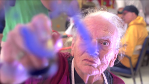 A senior man drawing in front of the camera