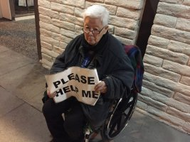 """an elderly asian individual in a wheelchair holds a sign reading """"please help me"""""""