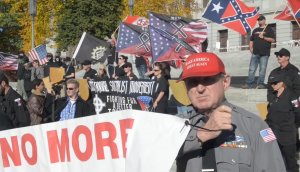 A man is holding a sign at an alt-right rally.