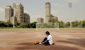 A teenager sitting in the middle of a soccer field.