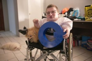 Fredrick Brennan sitting in wheelchair with his dog holding a blue 'Q' sign