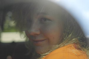 NSA Contractor sits in an orange jumpsuit in the back of a car.