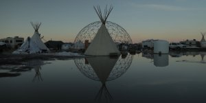 a white tipi sits in front of a steel geometric dome, both are reflected in a shallow pool at sunset.