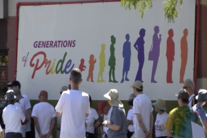 """retirees stand before a rainbow colored poster reading """"generations of pride."""""""