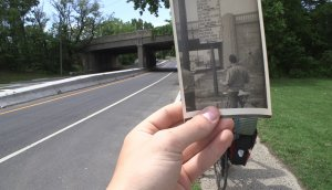 A hand holds an old photograph of a man with a bicycle at South Amboy Bridge. The photo lines up perfectly with South Amboy Bridge in the background.