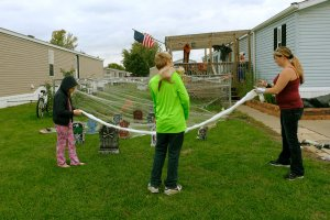 two young children hang Halloween decorations with their mother outside their mobile home