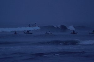 A group of Peruvian fishermen going into the ocean at dawn.