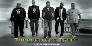 """Five middle-aged men walk down the boardwalk in """"exoneree band"""" t-shirts."""