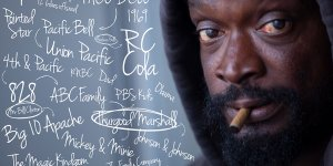 A Black unhoused man smokes a cigarette, handwritten thought maps surround his head.