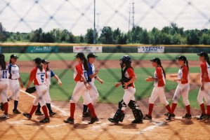opposing female baseball teams high five in the baseball field at the end of the game.