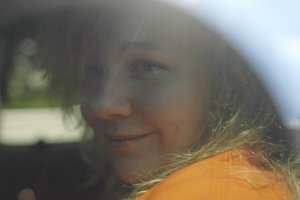 "A still from ""United States vs. Reality Winner"": A young woman with blonde hair and an orange sweatshirt looks out from the window of a car."