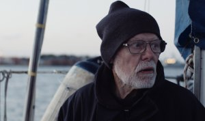 an older White man in glasses and a knit cap stands on the deck of a sailboat