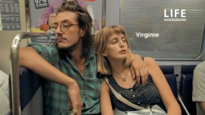 Two Caucasian couple is sitting in a metro subway.