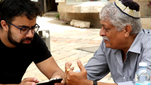 An older man in a yarmulka speaks with younger bearded man.