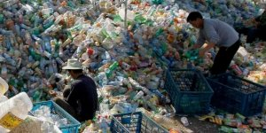 Two people searching through piles of plastic bottle