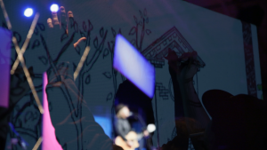 abstract superimposed image of fans raising their hands and a man playing guitar on stage.